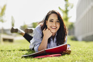 Portrait of smiling student lying on lawn with notebooks - JSMF00477