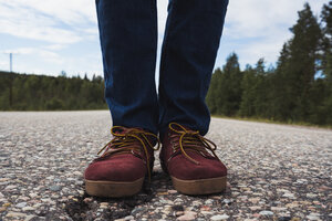 Finland, Lapland, feet of man standing on empty country road - KKAF02078