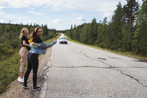 Finland, Lapland, two happy women hitchhiking at country road - KKAF02081