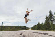 Finland, Lapland, exuberant young woman jumping in rural landscape - KKAF02084
