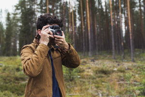 Finland, Lapland, man taking picture in rural landscape - KKAF02090