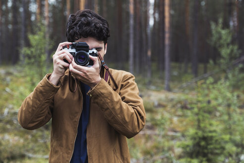 Finland, Lapland, man taking picture in rural landscape - KKAF02093