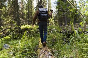 Finland, Lapland, man walking on log in forest - KKAF02102