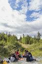 Finland, Lapland, friends having a picnic in rural landscape - KKAF02105