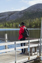 Finland, Lapland, man taking cell phone picture at the lakeside - KKAF02108