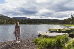 Finland, Lapland, woman wrapped in a blanket standing at the lakeside - KKAF02111