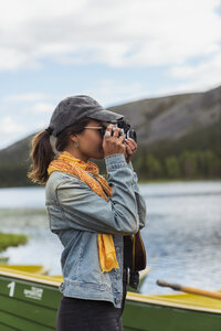 Finland, Lapland, woman taking picture with a camera at the lakeside - KKAF02120