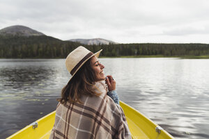 Finland, Lapland, happy woman wearing a hat on a boat on a lake - KKAF02123