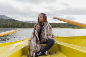 Finland, Lapland, woman wearing a blanket on a boat on a lake - KKAF02126