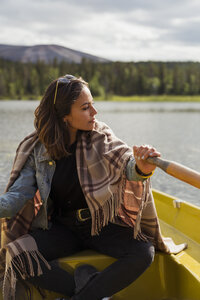 Finland, Lapland, woman wearing a blanket in a rowing boat on a lake - KKAF02129