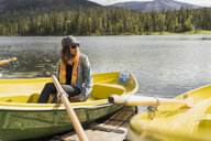 Finland, Lapland, woman sitting in a boat on a lake - KKAF02132