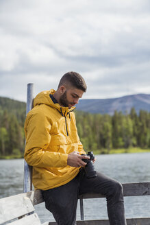 Finland, Lapland, young man with a camera on jetty at a lake - KKAF02135