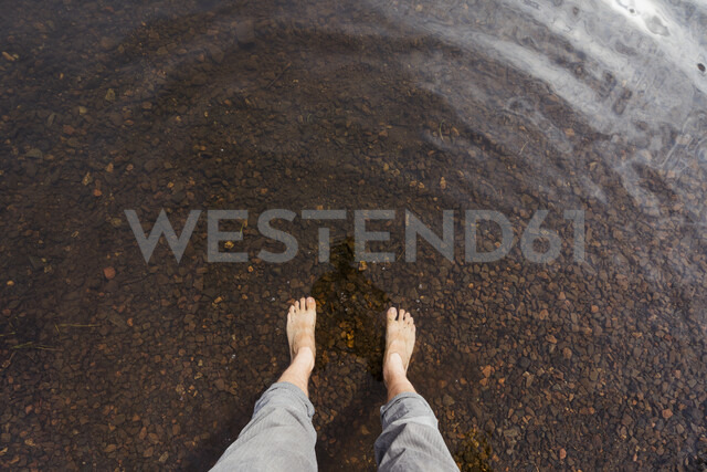 Feet of a man in water of a lake - KKAF02138
