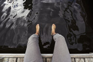 Man sitting on jetty at a lake dangling his feet in water - KKAF02141