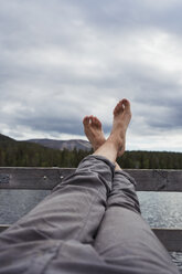 Man sitting on jetty at a lake holding his feet up - KKAF02144