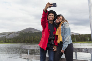 Finland, Lapland, happy couple on jetty at a lake taking a selfie - KKAF02147