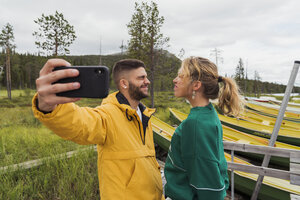 Finland, Lapland, young couple taking a funny selfie at the lakeside - KKAF02153