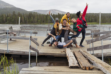 Finland, Lapland, portrait of happy playful friends posing on jetty at a lake - KKAF02159