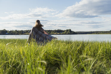 Finland, Lapland, woman wrapped in a blanket at the lakeside - KKAF02165
