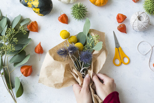 Autumnal decoration, ornamental pumpkins, hands wrapping bunch of flowers - JUNF01328