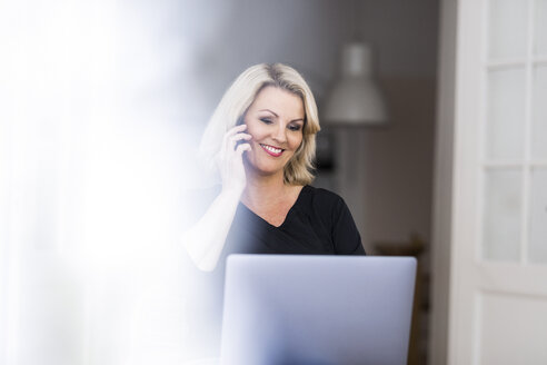 Portrait of smiling blond mature woman on the phone at home looking at laptop - FMKF05293