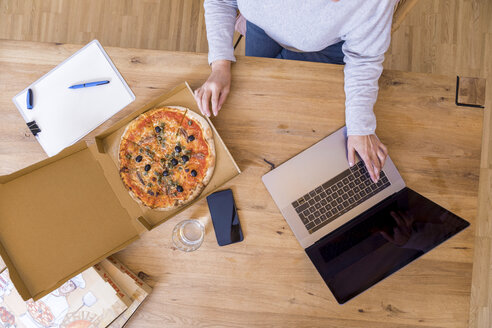 Woman at home office using laptop while eating pizza, top view - FMKF05305