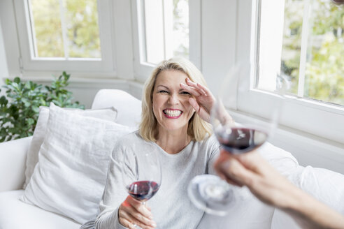 Portrait of laughing blond mature woman toasting with red wine at home - FMKF05314