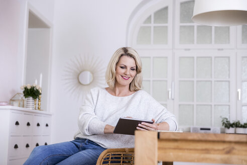 Portrait of smiling blond mature woman using digital tablet at home - FMKF05323