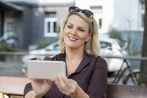 Portrait of smiling blond mature woman using smartphone outdoors - FMKF05332