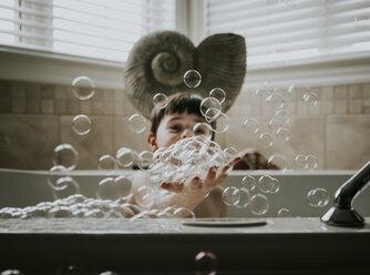 Boy playing with bubbles while taking bath in bathtub - CAVF48996