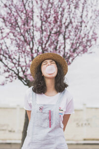 Young woman blowing bubble gum while standing against cherry tree at park - CAVF49014