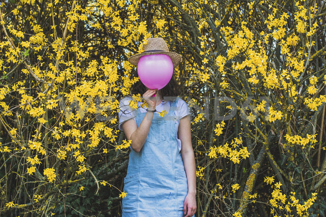 Playful young woman holding pink helium balloon with hat against face while standing by yellow blossoms at park - CAVF49017 - Cavan Images/Westend61