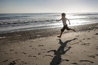 Full length of playful boy running at beach during sunset - CAVF49032