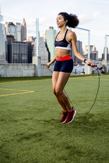 Female athlete exercising with jump rope on grassy field against buildings - CAVF49056