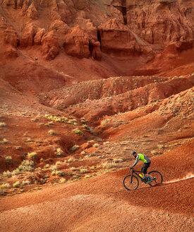 Side view of hiker mountain biking at desert - CAVF49086