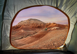 Mid distance view of hiker at desert seen through tent during sunset - CAVF49089