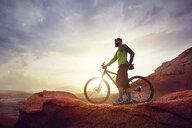 Full length of hiker with mountain bike standing on rocks against sky at desert during sunset - CAVF49092