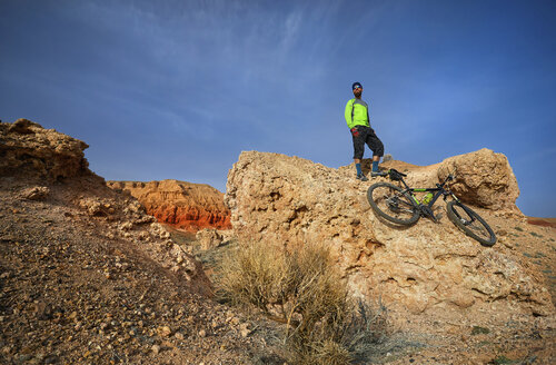 Low angle view of hiker standing on rock formation with mountain bike at desert - CAVF49095