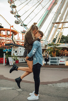Happy young couple embracing and kissing at a funfair - LHPF00088