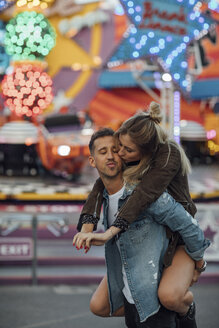 Young couple in love, embracing at a funfair - LHPF00100
