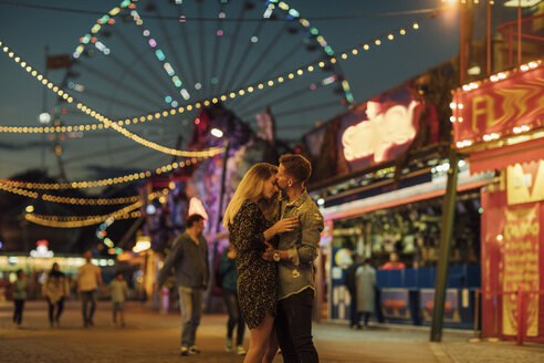 Happy young couple embracing and kissing at a funfair - LHPF00112