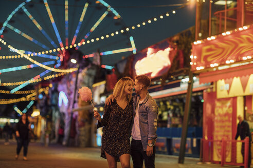 Happy young couple embracing and kissing at a funfair - LHPF00115