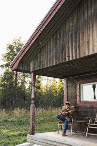Young man sitting on veranda of a wood house, playing the ukulele - KKAF02178