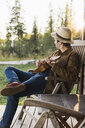 Young man sitting on veranda of a wood house, playing the ukulele - KKAF02181