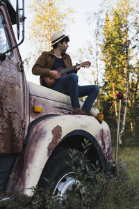 Young amn sitting on a broken truck, playing the ukulele - KKAF02184