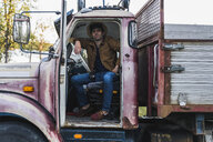 Cool young man sitting in a broken truck - KKAF02187