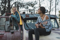 Two friends sitting on a broken truck, playing the ukulele - KKAF02196