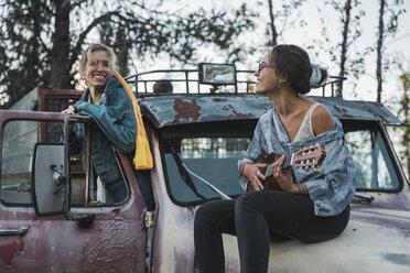 Two friends sitting on a broken truck, playing the ukulele - KKAF02196