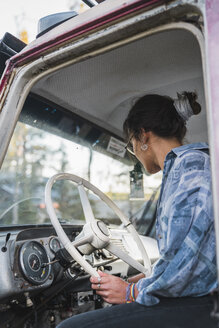 Young woman sitting in cabin of a broken vintage truck - KKAF02199