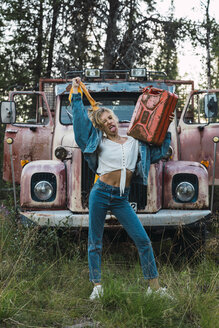Young woman posing at a broken vintage truck, holding petrol can - KKAF02202